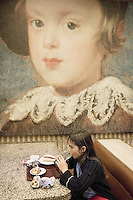 Spain. Province of Madrid. Madrid. Micaela Ruef drinks a glass of water and eats pastries at the cafeteria of the Museo Nacional del Prado (Prado Museum). A poster of a previous exhibit on Spanish Paintings and showing the portrait of a young girl is fixed on the wall. The Prado Museum is considered to be one of the world´s best art galleries and mueum. MODEL RELEASED. © 2007  Didier Ruef