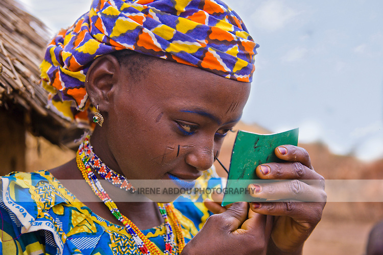 A young Fulani woman in the village of Bele Kwara in southwestern Niger applyies blue makeup.