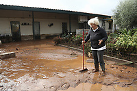 Pictured: A homeowner tries to clear debris from her driveway.<br /> Re: Five people have reportedly died and severe damage caused by heavy rain and flash flooding in the area of Mandra, near Athens, Greece. Wednesday 15 November 2017