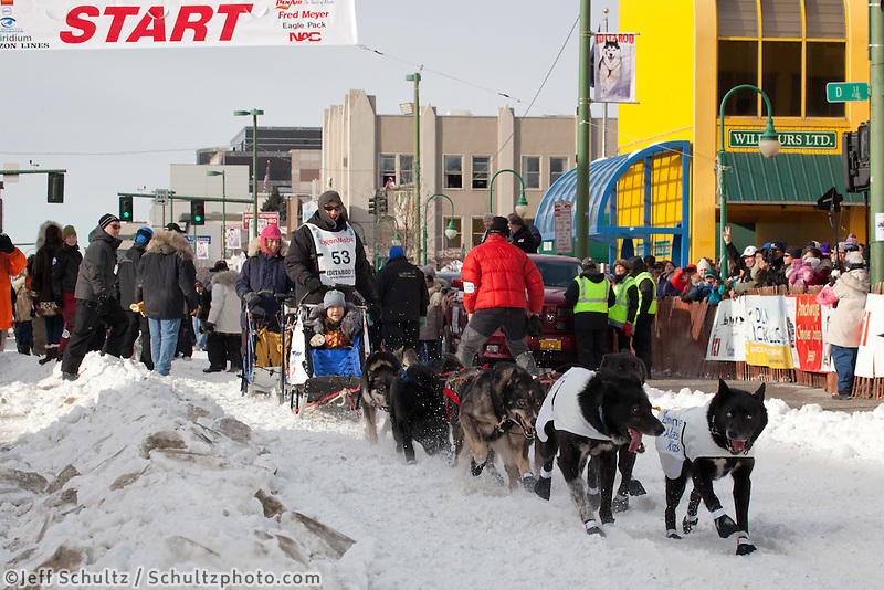 Musher John Baker and Iditarider.leave the 2011 Iditarod ceremonial start line in downtown Anchorage, Alaska