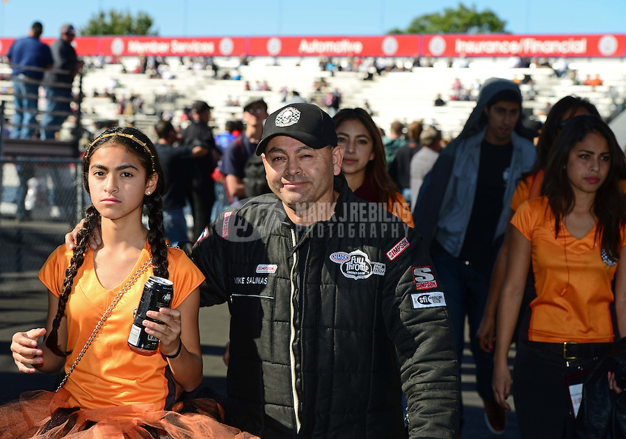 Nov. 11, 2012; Pomona, CA, USA: NHRA top fuel dragster driver Mike Salinas with daughters during the Auto Club Finals at at Auto Club Raceway at Pomona. Mandatory Credit: Mark J. Rebilas-