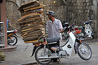 Man carrying cardboard on the back of his scooter, Hanoi, Vietnam