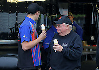 May 3, 2013; Commerce, GA, USA: Crew members for NHRA top fuel dragster driver Pat Dakin (not pictured) eat ice cream cones during a rain delay to qualifying for the Southern Nationals at Atlanta Dragway. Mandatory Credit: Mark J. Rebilas-