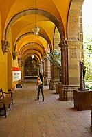 Student walking down a passageway in the Escuella  de las Bellas Artes or El Nigromante, San Miguel de Allende, Mexico