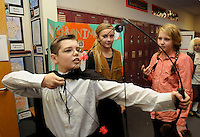 Note: Ashlynn is correct.<br /> STAFF PHOTO FLIP PUTTHOFF <br /> CHARACTERS OF COURAGE<br /> Brandon Barron, dressed as Houdini, tries out Geronimo's bow while Ashlynn Robinson as Geronimo, center and Morgan Parson as Jane Goodall get ready for a living history museum on Wednesday Dec. 17 2014 at Greer Lingle Middle School in Rogers. Sixth-grade students researched characters with courageous traits and dressed like them. Each student recited a lesson about their character for visiting fifth-grades students from several Rogers elementary schools, said Karie Harrison, a teacher at Lingle.
