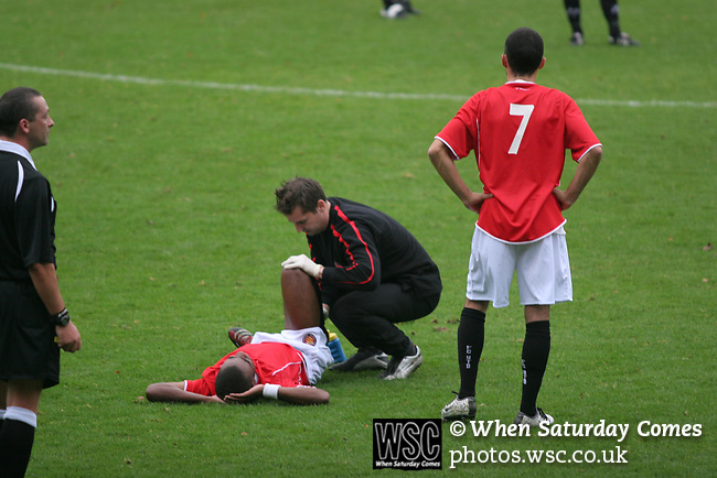 FC United of Manchester 8, Glossop North End 0, 28/10/2006. Gigg Lane, Bury, North West Counties League division one. An FC United of Manchester footballer lying injured and receiving treatment during his side's 8-0 defeat of Glossop North End in a North West Counties division one match at United's home stadium, Gigg Lane, home to Bury FC. The match was staged on People United Day, an event started in 1999 which brought together fans from across Europe to campaign against racism. FC United were formed in the summer of 2005 by supporters of Manchester United in response to the take over of their club by American millionaire Malcolm Glazer and his family. The club entered the football pyramid at the lowest level with the intention to climbing through the leagues. FCUM won the match 8-0, watched by 3257 spectators. Photo by Colin McPherson.