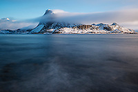 Offersøykammen mountain peak rises from turbulent waters of Nappstraumen, Lofoten Islands, Norway