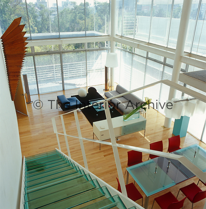 View looking down the glass staircase from the mezzanine to the double-height glass-walled living area which is furnished with Italian pieces