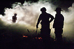 MICHAEL SMITH/WTE.Members of Laramie County Fire District 1 and the Cheyenne Fire Department take a breather as they wait for a truck with more water to battle a grass fire off Lincolnway and North American Road  late Monday night.  Firefighters quickly took control of the small blaze and the cause is still under investigation.