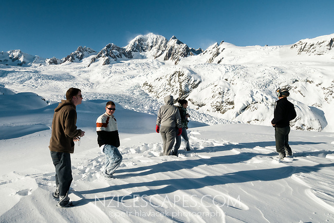 Tourists admiring and enjoying spectacular beauty of Southern Alps after their helicopter landing at Fox Glacier, Westland Tai Poutini National Park, West Coast, UNESCO World Heritage Area, New Zealand, NZ