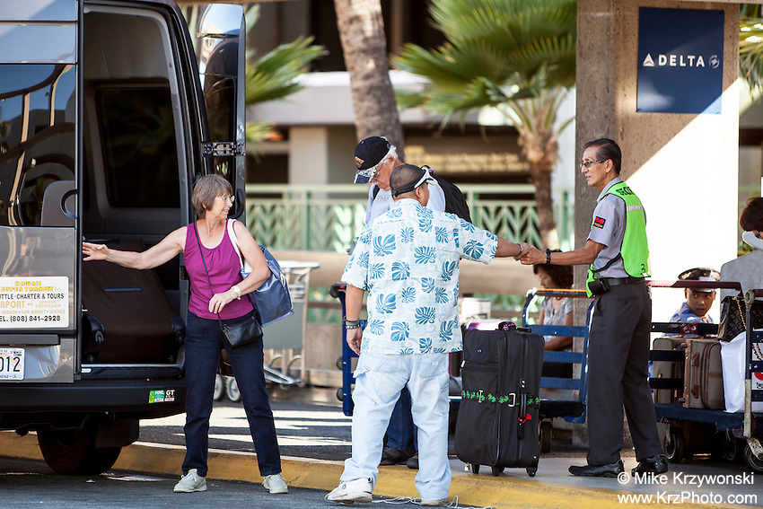 Shuttle van driver shaking hands w/ security guard at the Honolulu International Airport, Oahu, Hawaii