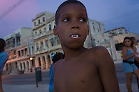 boy with plastic vamire teeth at Malecon, sunset time.