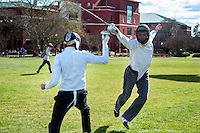 Skye Cooley, assistant professor of communication, springs to his attack during a fencing demonstration on the Drill Field. The fencing club meets three nights per week at the Sanderson Center on campus. <br />