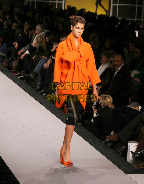 MODEL.Ungaro Ready to Wear Autumn/Winter Fashion Show Collection 2005/2006, Paris, France, March 1st 2005..full length runway catwalk orange top bow tied over-sized shoes.**UK SALES ONLY**.Ref: MDS.www.capitalpictures.com.sales@capitalpictures.com.©Virgille Biechy/O.Medias/Capital Pictures .
