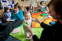 "A breastfeeding consultant on the telephone arranging a tongue-tie division while one of the mothers plays with her baby  at a drop-in breastfeeding support centre.<br /> <br /> Image from the ""We Do It In Public"" documentary photography project collection: <br />  www.breastfeedinginpublic.co.uk<br /> <br /> Dorset, England, UK<br /> 17/04/2013"