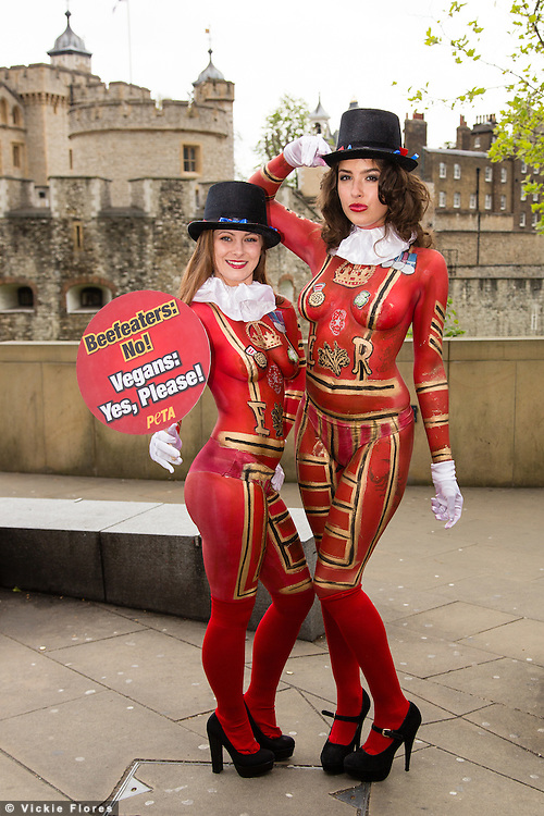 "Two female PETA demonstrators with their bodies painted to look like ""Beefeaters"" (Yeoman Warder) stand outside the Tower of London asking people to give up eating meat. The campaign has been timed to fall one day before St George's Day."