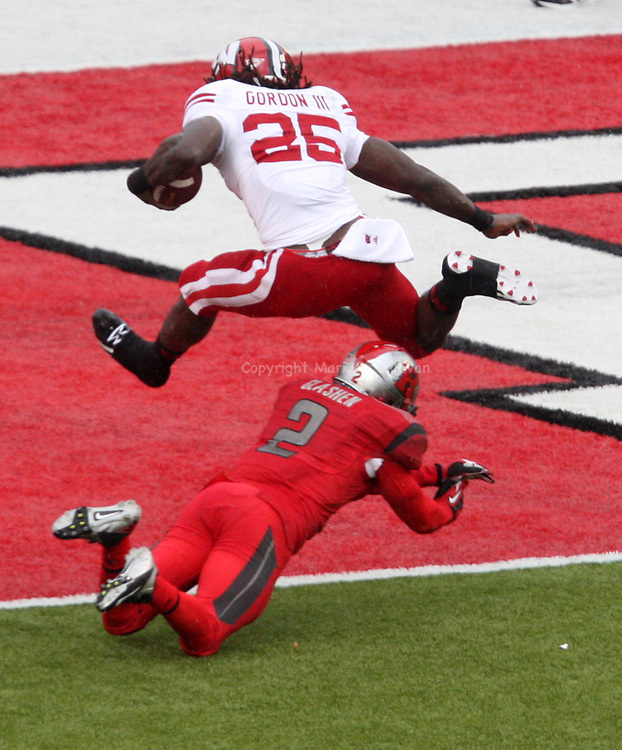 Big Ten Football game at High Point Solutions Stadium in Piscataway has the Scarlet Knights of Rutgers taking on the Badgers of Wisconsin <br /> <br /> <br /> Wisconsin's # 25 Melvin Gordon III leaps over the diving tackle attempt of Rutgers # 2 Gareef Glashen for the touchdown during the 1st half of play. <br /> <br /> On Saturday November 1,2014<br /> Photo: Mark R. Sullivan/Staff Photographer