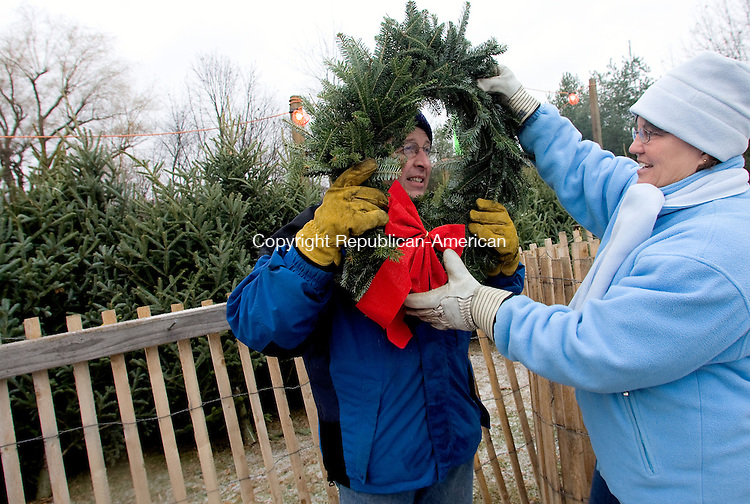 TORRINGTON, CT - 30 NOVEMBER 2008 -113008JT03-<br /> Torringford Volunteer Fire Department Auxiliary member Kathy Newkirk holds a wreath up to volunteer Tom Whittaker's face before Newkirk purchased the wreath during the fire department's first day of its annual Christmas tree sale on Sunday in Torrington. The department usually holds the event the weekend after Thanksgiving, choosing local farms from which to purchase the trees. This year the trees are from a Christmas tree farm in Voluntown. The sale will continue until everything is sold.<br /> Josalee Thrift / Republican-American