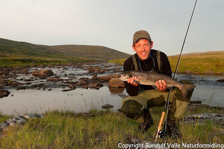 Fisker og laks fanget i en liten Finnmarkselv. ---- Angler and salmon.
