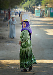 A woman carries water on her head as she walks through the Egyptian village of Kafr Darwish.