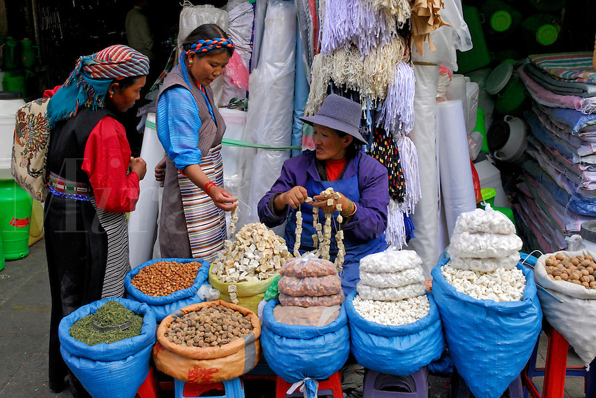 Tibetan housewives, wearing typical striped aprons, buying stringed cubes of yak cheese, or chura, at Tromsikhang Market in the Barkhor area of Lhasa, Tibet.