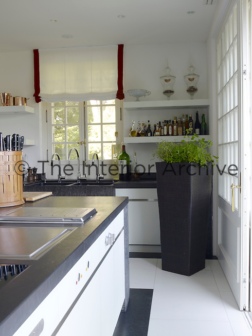 The modern kitchen is in contrast to the rest of the villa and comprises white lacquer cabinets and slate worktops