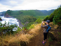 A woman tourist takes a picture of Pololu Valley and its beach with her smart phone from a hiking trail, Hawi, Island of Hawai'i.
