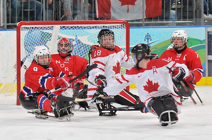 Both Greg Westlake (12) and Billy Bridges (18) try to deflect this puck during the 2010 Paralympic Games, bronze medal sledge hockey game at UBC Thunderbird Arena in Vancouver. Credit: CPC/HC/Matthew Manor.