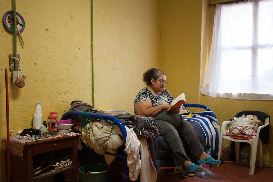 "María Isabel, a resident of Casa Xochiquetzal, reads a book of Vladimir Nabokov in her bedroom at the shelter in Mexico City, Mexico on April 19, 2012. María Isabel, who grew up in Michoacán, Mexico, ran away from home at the age of 9 after a year in which her father ""used her."" When she got to the Mexico City bus station, she met a woman selling tamales who offered her a home and education. María Isabel nearly finished her studies to become a teacher, but when her caretaker died, she became a sex worker at 17. She now reads, writes poetry, embroiders, and makes earrings and bracelets. Casa Xochiquetzal is a shelter for elderly sex workers in Mexico City. It gives the women refuge, food, health services, a space to learn about their human rights and courses to help them rediscover their self-confidence and deal with traumatic aspects of their lives. Casa Xochiquetzal provides a space to age with dignity for a group of vulnerable women who are often invisible to society at large. It is the only such shelter existing in Latin America. Photo by Bénédicte Desrus"