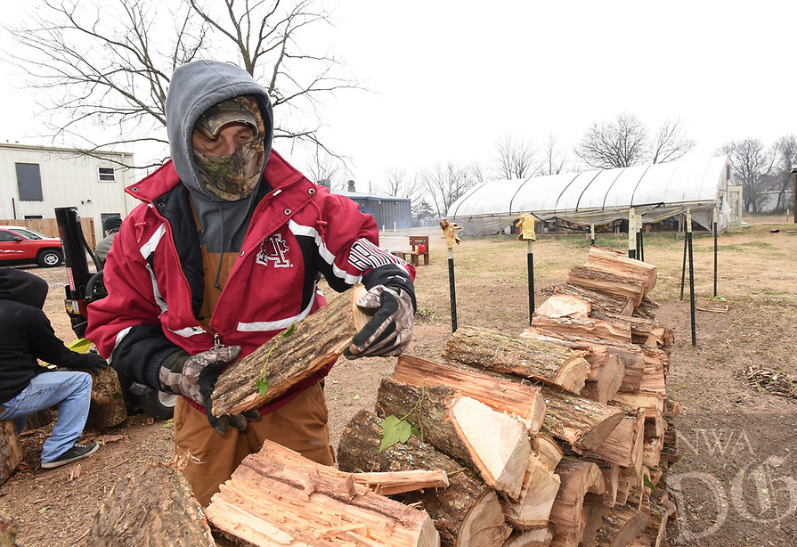 NWA Democrat-Gazette/FLIP PUTTHOFF<br /> HOT COMMODITY<br /> Joey Cox stacks firewood on Saturday Dec. 30 2017 at Soul's Harbor in Rogers. Cox worked with a crew cutting and splitting firewood, which is available for purchase at Soul's Harbor, 1206 N. Second St. Firewood sales have been brisk this winter, Cox said.