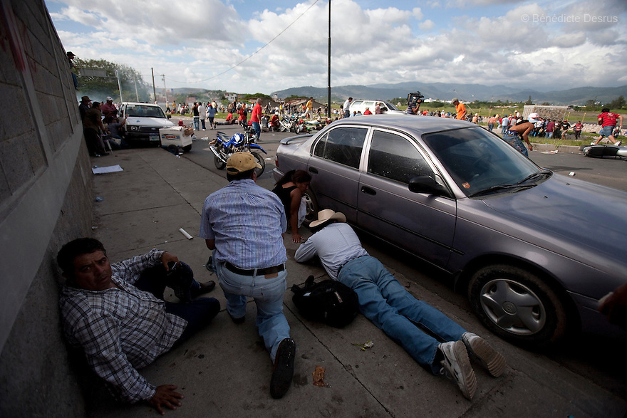 5 July 2009 - Tegucigalpa, Honduras - Supporters of ousted Honduras' President Manuel Zelaya lie as soldiers fire tear gas  and live bullets at a protest at the international airport in Tegucigalpa. At least one person was killed and ten were badly wounded in Honduras on Sunday when protesters demanding the return of Zelaya clashed with troops at the main airport in the capital. Photo credit: Benedicte Desrus