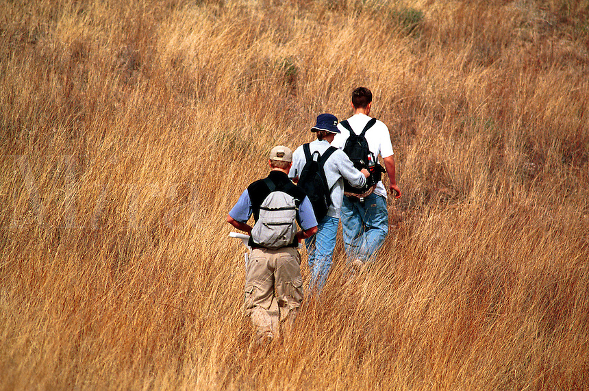 Orienteering classroom outdoors, teenage male students walking in tall grass. High School Students. Sonoita Arizona United States National Forest In Southwest.