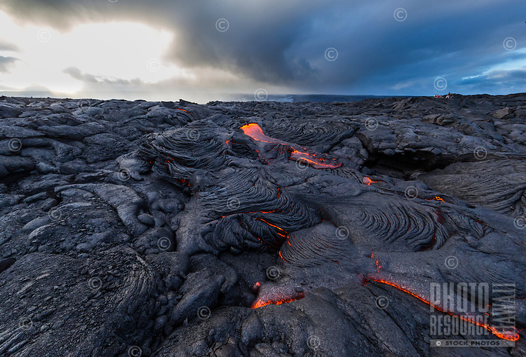 The sun sets behind glowing lava in the expansive fields of Hawai'i Volcanoes National Park, Hawai'i Island. Visitors on the distant right enjoy the view.