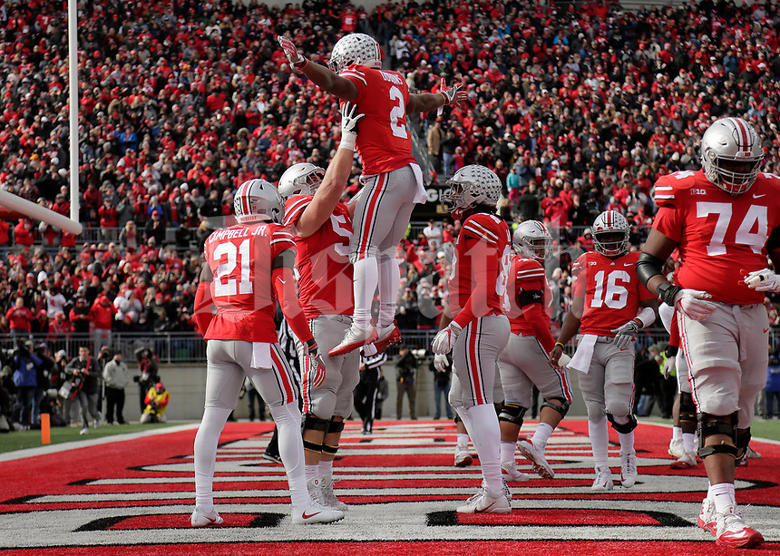 Ohio State Buckeyes offensive lineman Billy Price (54) lifts running back J.K. Dobbins (2) after scoring a touchdown during the second quarter of the NCAA football game against the Michigan State Spartans at Ohio Stadium in Columbus on Nov. 11, 2017. [Adam Cairns/Dispatch]