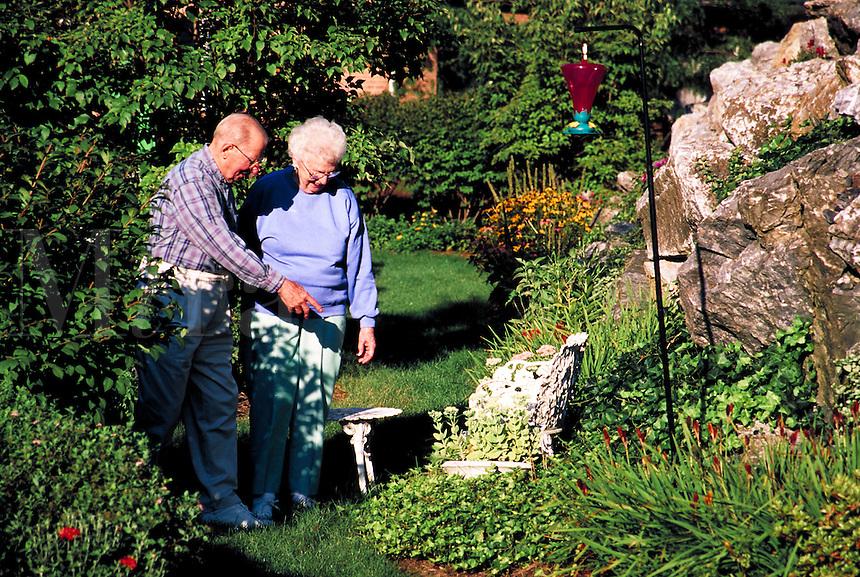 Senior couple touring and admiring their flower garden.