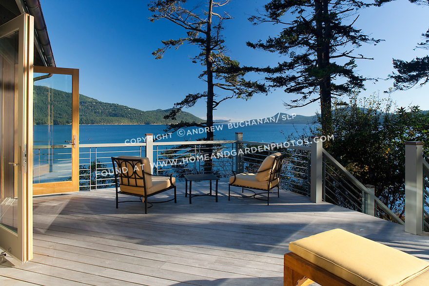 French doors open onto an expansive deck with beautiful water views. this image is available through an alternate architectural stock image agency, Collinstock located here: http://www.collinstock.com