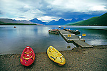 Kayaks on shore and boats float at a dock on placid scenic Lake McDonald with mountains on a cloudy summer day in Glacier National Park in Montana USA