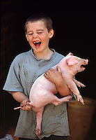 A smiling young boy holds a squealing piglet.