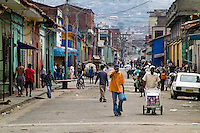 People pass along the main street in the slum of Calvario, Cali, Colombia, 5 April 2004. Calvario, a slum right in the centre of the city, is considered the social bottom of Cali society. Poor dwellers recollect the garbage in the near city centre to sell it for recycling, while their children get high by sniffing the shoe glue on the dirty streets of ghetto. The order in Calvario is maintained by the illegal authorities, usually former policemen or army members, who set their own rules. Criminality, drug abuse, unemployment never allow the slum people jump off the misery and stop being the second category citizen within the rigid society of Colombia. Although Christian missionary organizations attempt to provide help, the overall situation does not improve.