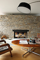 The central fireplace that divides the living room is designed in a 50s style and built from Pyrennean stone