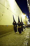Hooded penitents going to the church before a Holy Week procession, Seville, Spain