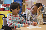 Oakland CA Aide helping developmentally disabled primary school student in wheelchair with her classroom assignment in special education classroom  MR