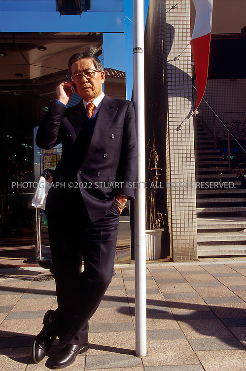 11/28/00--Tokyo, Japan..Former Peruvian president Alberto Fujimori speaking on a mobile phone in a quiet surburban neighborhood of Tokyo, Japan. Fujimori recently took refuge in Japan following his ouster from power...All photographs ©2003 Stuart Isett.All rights reserved.This image may not be reproduced without expressed written permission from Stuart Isett.