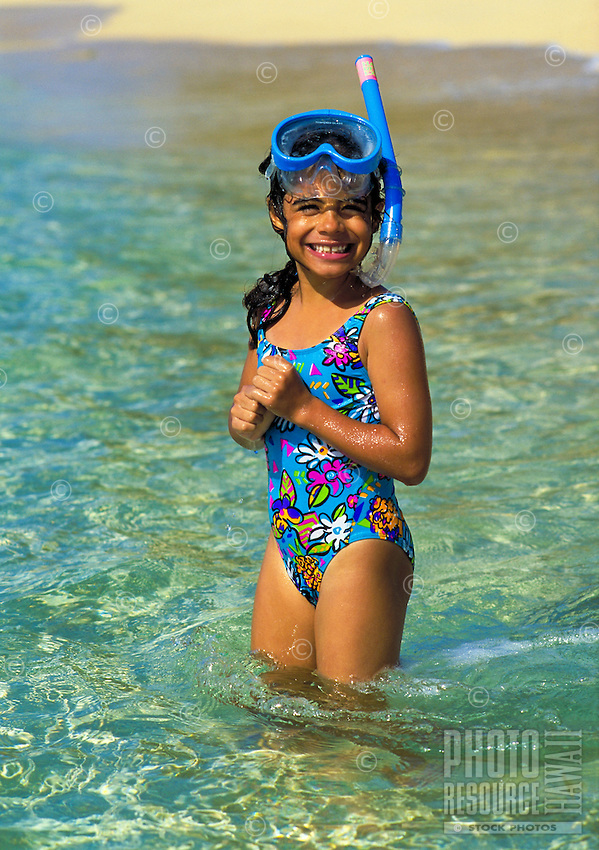 Portrait of a young local girl with mask and snorkel standing in clear water near the shore of at beach on Oahu.