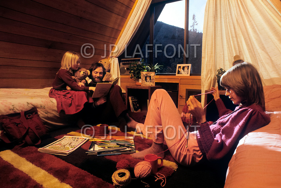 Wasco, Oregon, February 1984: A family at home in Rajneeshpuram. Swami Antar Svargo, 33 yrs, Ma Deva Shantam, 35 yrs and Ma Dhyan Deepta, 9 yrs. Settled in Rajneeshpuram in May 1982. Rajneeshpuram, was an intentional community in Wasco County, Oregon, briefly incorporated as a city in the 1980s, which was populated with followers of the spiritual teacher Osho, then known as Bhagwan Shree Rajneesh. The community was developed by turning a ranch from an empty rural property into a city complete with typical urban infrastructure, with population of about 7000 followers.