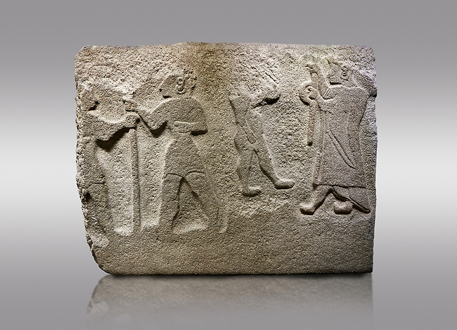 Alaca Hoyuk Hittite monumental relief sculpted orthostat stone panel. Andesite, Alaca, Corum, 1399 - 1301 B.C. Anatolian Civilizations Museum, Ankara, Turkey<br /> <br /> The rightmost figure wears a long coat and tailed dress. With both hands, he holds a sceptre with a ring in the middle. This item is thought to be a cult object in Assyria reliefs. The pointed and twisted tips of his shoes also show that he is in a high rank.  <br /> <br /> Against a brown gray background.