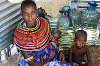 KENYA, Marsabit, Samburu village Merille, Samburu woman and her children with water plastic drum, water has to be collected in droughts from far distances by women / KENIA, Marsabit, Samburu Dorf Merille, Samburu Frau mit Kindern vor Wasservoprrat, Wasser muss in Duerrezeiten ueber weite Entfernungen von Frauen heran getragen werden