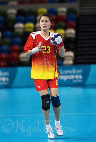 23 NOV 2011 - LONDON, GBR - China's Wu Yin (#23, in red and yellow) prepares to pass the ball during the 2011 London Handball Cup match against Slovakia at The Handball Arena in the Olympic Park in Stratford, London  (PHOTO (C) NIGEL FARROW)
