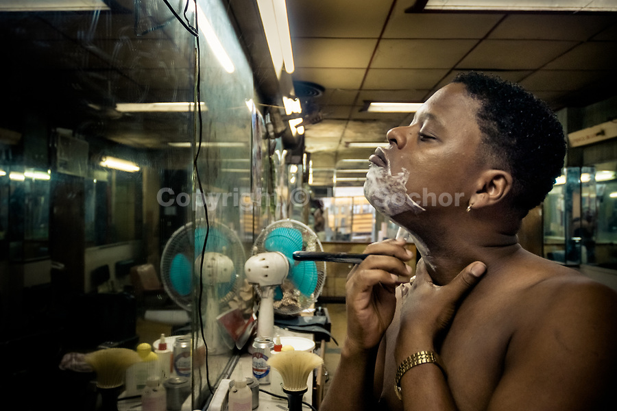 A young Cuban hairdresser shaves himself with a razor after a busy working day in a barber shop in Havana, Cuba, 16 August 2008.