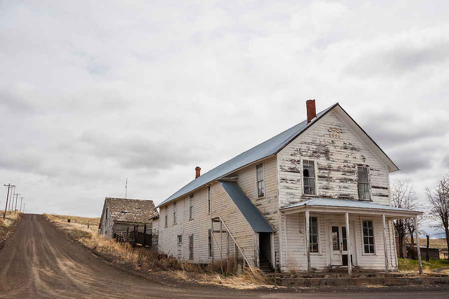 An abandoned house is seen in Mayville, Oregon with the Carter Hill Road stretching off into the distance in Gilliam County.